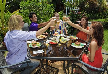 friends at a backyard bar-b-que in hawaii raising their glasses in a toast
